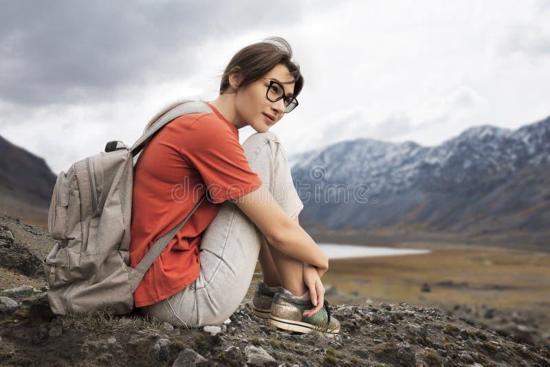 Ο ταξιδιώτης γυναικών εξετάζει την απόσταση στα χιονώδη βουνά Θερινά ενδύματα και ένα σακίδιο πλάτης στους ώμους στοκ φωτογραφία
