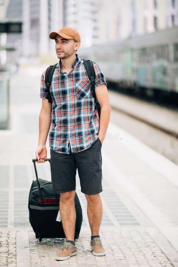Ο ταξιδιώτης είναι πρώην στο σταθμό τρένου Ο νεαρός άνδρας με το σακίδιο πλάτης και τη βαλίτσα έχασε το τραίνο και την αναμονή έπ στοκ εικόνες