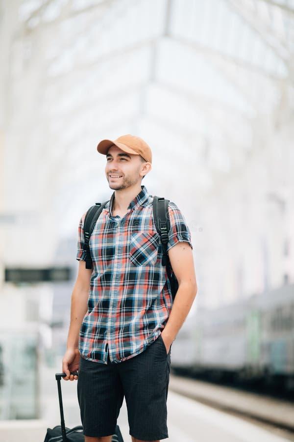 Ο ταξιδιώτης είναι πρώην στο σταθμό τρένου Ο νεαρός άνδρας με το σακίδιο πλάτης και τη βαλίτσα έχασε το τραίνο και την αναμονή έπ στοκ φωτογραφία με δικαίωμα ελεύθερης χρήσης