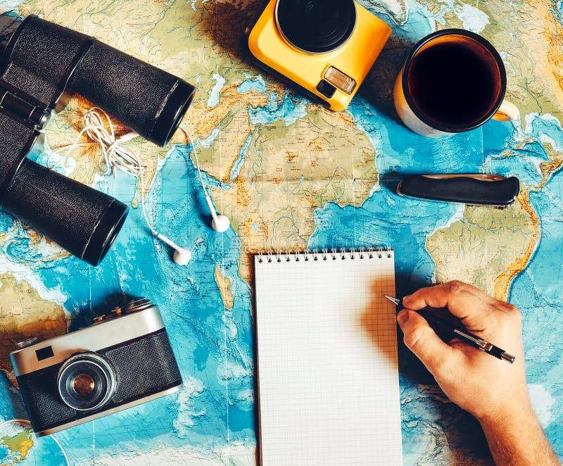 Ο ταξιδιώτης κάνει ένα σχέδιο ταξιδιού εργαλείο στρατοπέδευσης, τοπ άποψη στοκ εικόνα