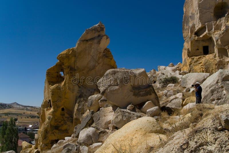 Ο ταξιδιώτης με μια κάμερα φωτογραφίζει τις καταστροφές της αρχαίας πόλης Cavusin στοκ φωτογραφίες με δικαίωμα ελεύθερης χρήσης