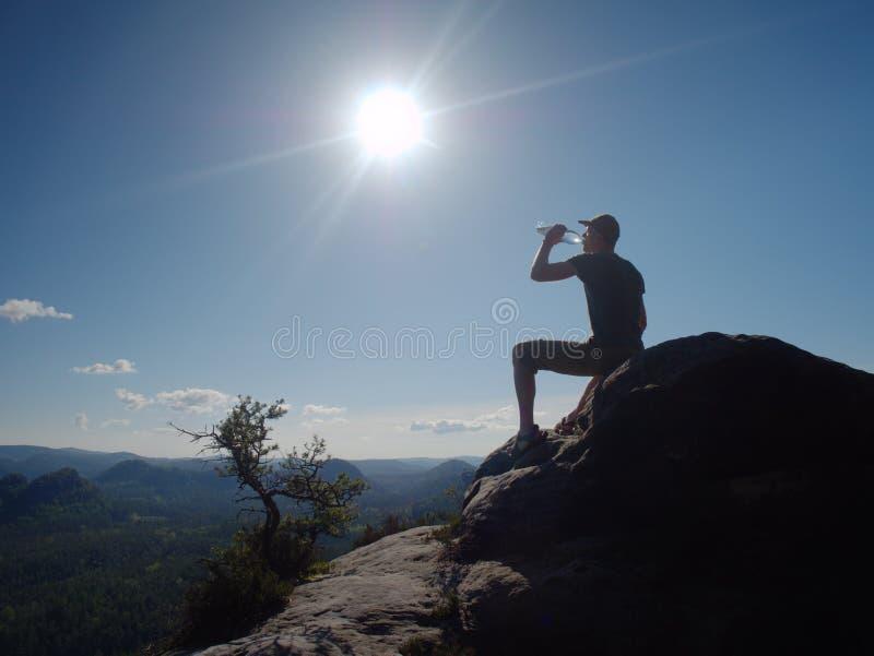 Ο ταξιδιώτης οδοιπόρων ατόμων πίνει το νερό με την άποψη του βουνού στοκ εικόνες