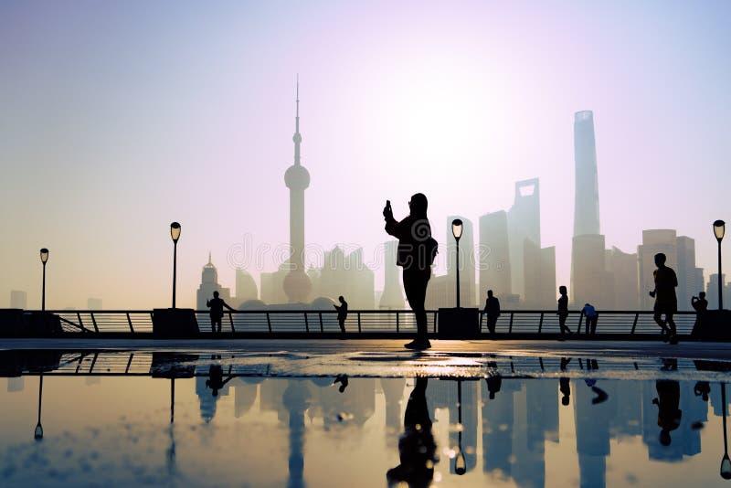 Ο ταξιδιώτης παίρνει μια φωτογραφία της δραστηριότητας πρωινού στο φράγμα, όχθη ποταμού huangpu, υπόβαθρο άποψης πόλεων της Σαγγά στοκ φωτογραφία