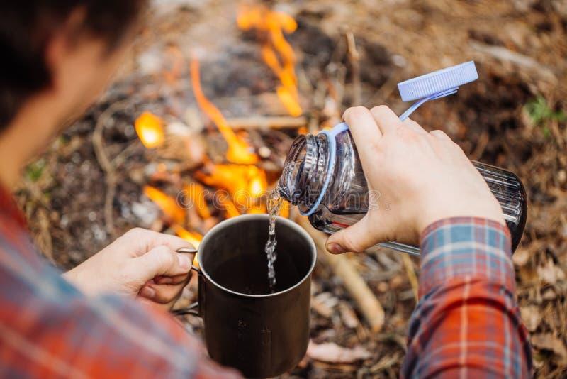 Ο ταξιδιώτης ατόμων χύνει το νερό από ένα μπουκάλι σε μια κούπα μετάλλων στοκ εικόνες