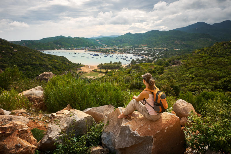 Ο ταξιδιώτης γυναικών εξετάζει την άκρη του απότομου βράχου στον κόλπο θάλασσας του mounta στοκ φωτογραφία με δικαίωμα ελεύθερης χρήσης