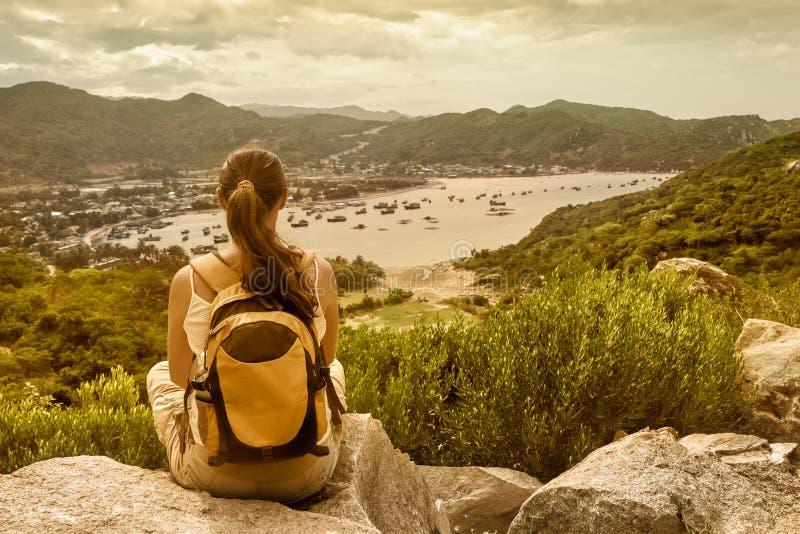Ο ταξιδιώτης γυναικών κάθεται και εξετάζει την άκρη του απότομου βράχου στο s στοκ εικόνες
