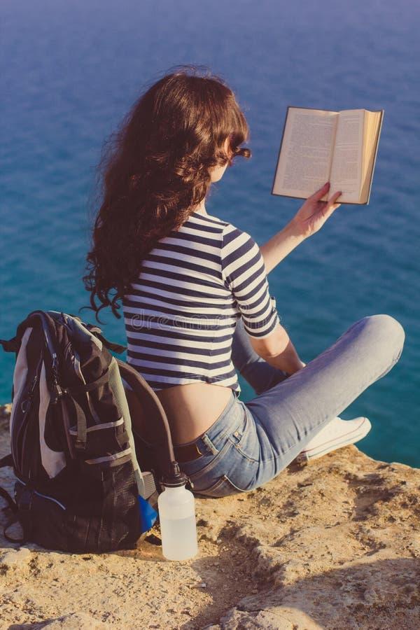 Ο ταξιδιώτης κοριτσιών κάθεται στην αιχμή mounrain και διαβάζει το βιβλίο στοκ φωτογραφία με δικαίωμα ελεύθερης χρήσης