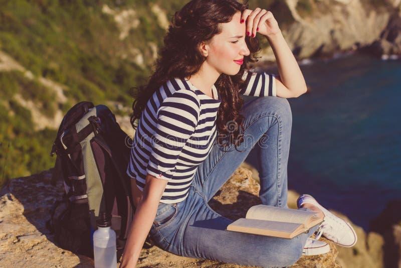 Ο ταξιδιώτης κοριτσιών κάθεται στο βράχο και διαβάζει το βιβλίο στοκ εικόνες