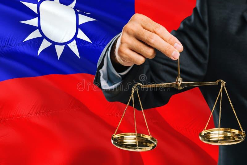 Ο ταϊβανικός δικαστής κρατά τις χρυσές κλίμακες της δικαιοσύνης με το κυματίζοντας υπόβαθρο σημαιών της Ταϊβάν Θέμα ισότητας και  στοκ φωτογραφία με δικαίωμα ελεύθερης χρήσης