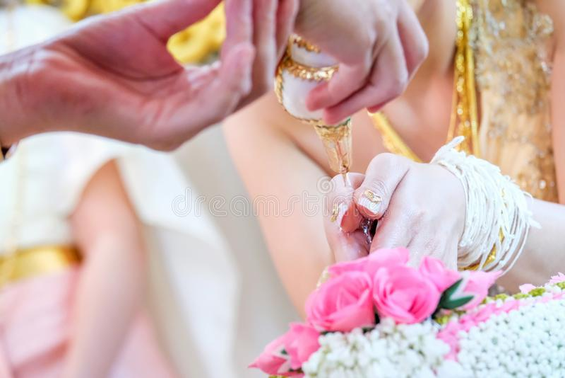 Ο ταϊλανδικός γάμος, κλείνει επάνω των χεριών που χύνουν το νερό στα χέρια στοκ φωτογραφίες
