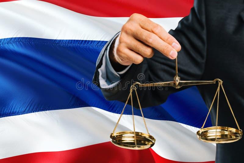 Ο ταϊλανδικός δικαστής κρατά τις χρυσές κλίμακες της δικαιοσύνης με το κυματίζοντας υπόβαθρο σημαιών της Ταϊλάνδης Θέμα ισότητας  στοκ εικόνες