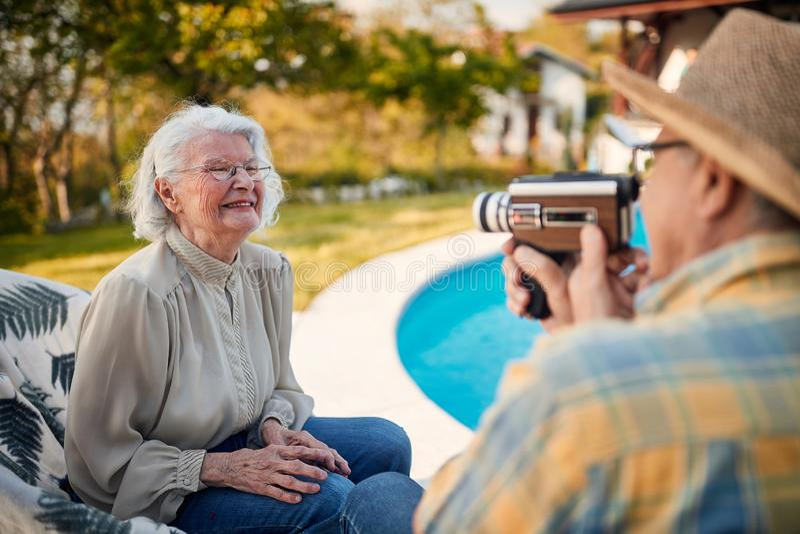 Ο τελειόφοιτος στις διακοπές και πιάνει με μια κάμερα τη γυναίκα του στοκ εικόνα