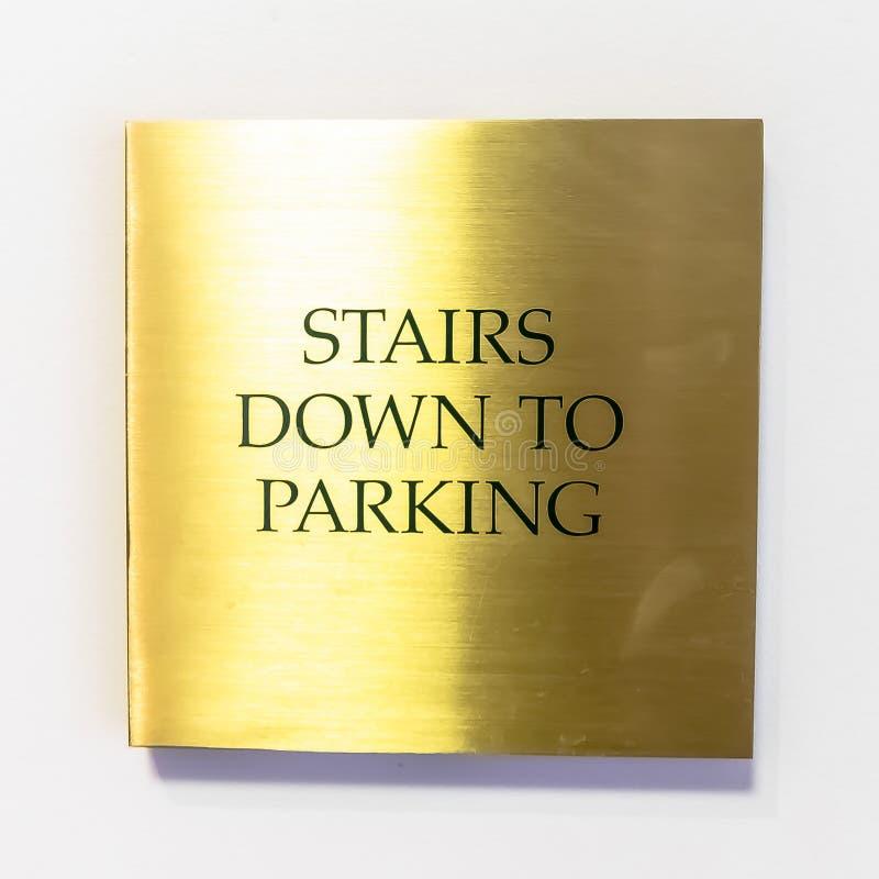 Ο τετραγωνικός χρυσός κάλυψε το σημάδι που διαβάζει τα σκαλοπάτια κάτω στο χώρο στάθμευσης ενάντια στον άσπρο εσωτερικό τοίχο στοκ εικόνες
