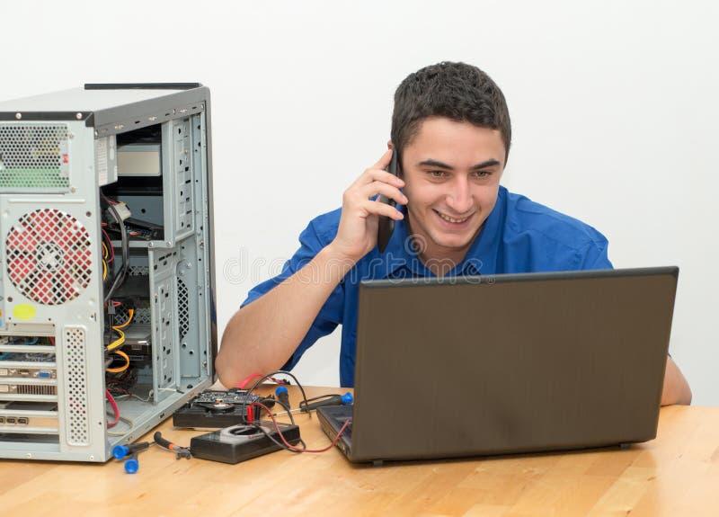 Ο τεχνικός νεαρών άνδρων που εργάζεται στο σπασμένο υπολογιστή και καλεί τα cus στοκ φωτογραφίες με δικαίωμα ελεύθερης χρήσης