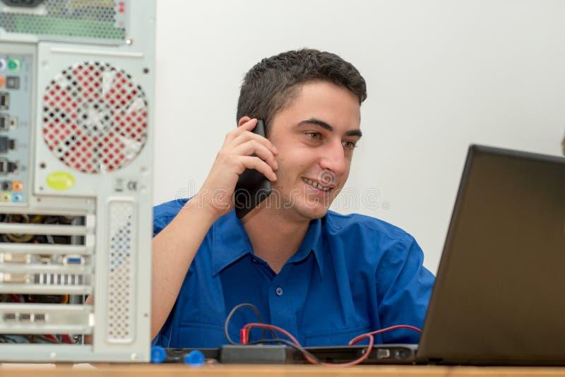 Ο τεχνικός νεαρών άνδρων που εργάζεται στο σπασμένο υπολογιστή και καλεί τα cus στοκ εικόνα με δικαίωμα ελεύθερης χρήσης