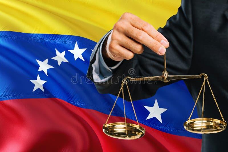Ο της Βενεζουέλας δικαστής κρατά τις χρυσές κλίμακες της δικαιοσύνης με το κυματίζοντας υπόβαθρο σημαιών της Βενεζουέλας Θέμα ισό στοκ εικόνες