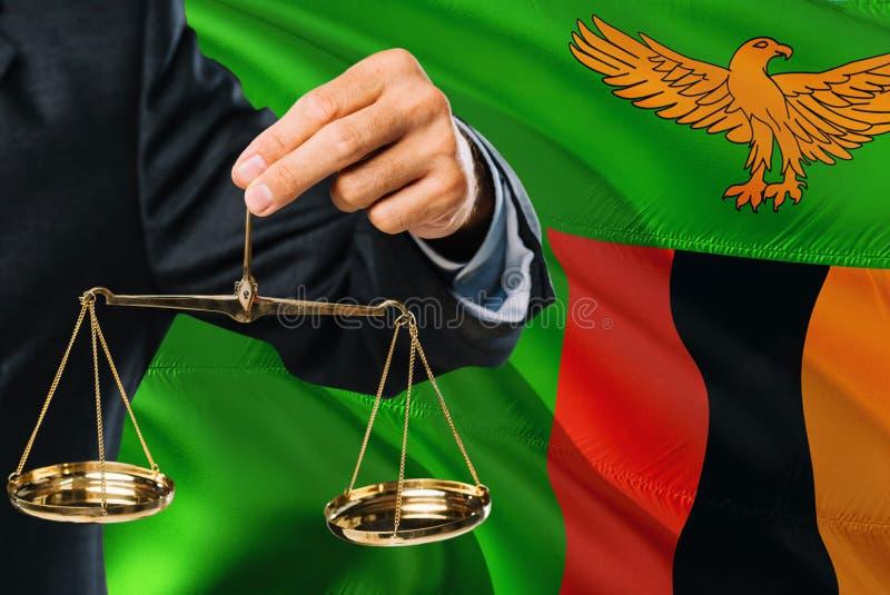 Ο της Ζάμπια δικαστής κρατά τις χρυσές κλίμακες της δικαιοσύνης με το κυματίζοντας υπόβαθρο σημαιών της Ζάμπια Θέμα ισότητας και  στοκ φωτογραφία με δικαίωμα ελεύθερης χρήσης