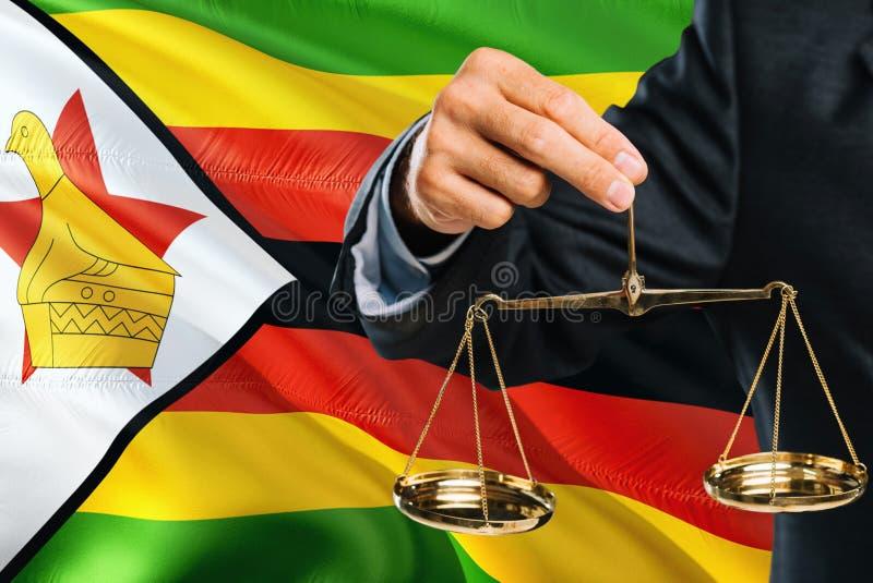 Ο της Ζιμπάμπουε δικαστής κρατά τις χρυσές κλίμακες της δικαιοσύνης με τη Ζιμπάμπουε που κυματίζει το υπόβαθρο σημαιών Θέμα ισότη στοκ εικόνες