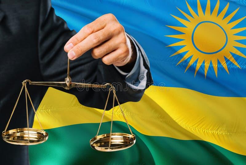 Ο της Ρουάντα δικαστής κρατά τις χρυσές κλίμακες της δικαιοσύνης με το κυματίζοντας υπόβαθρο σημαιών της Ρουάντα Θέμα ισότητας κα στοκ εικόνες με δικαίωμα ελεύθερης χρήσης