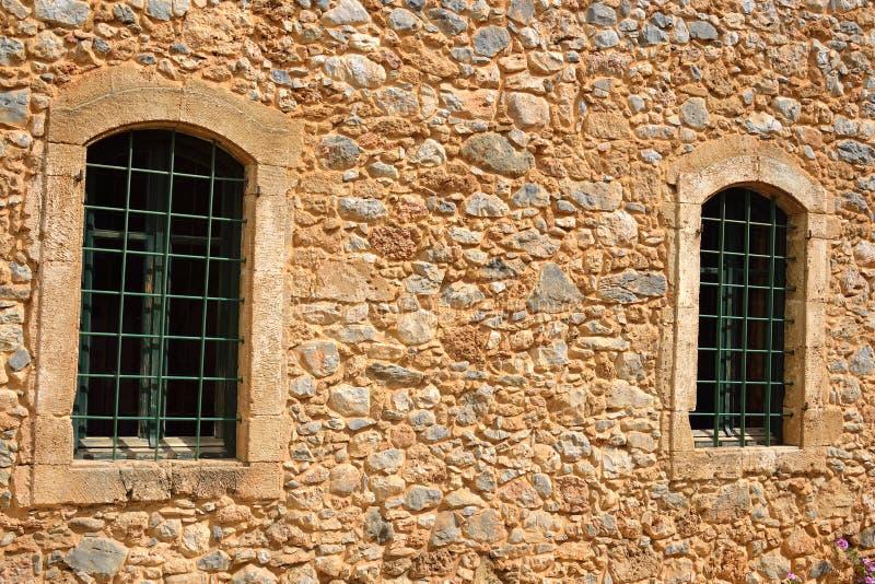 Ο τοίχος ενός παλαιού σπιτιού με δύο παράθυρα στοκ εικόνες