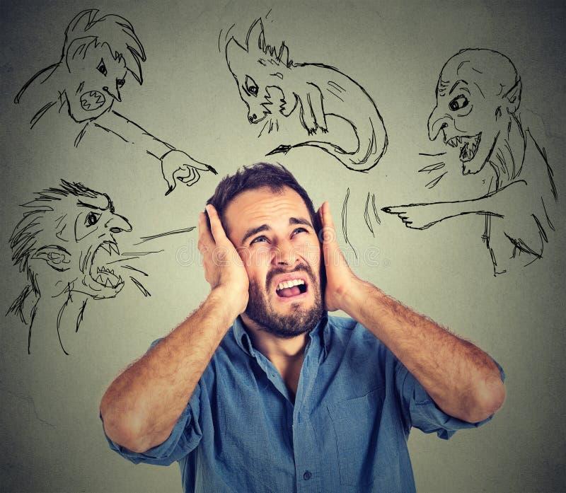 Ο τονισμένος νεαρός άνδρας καλύπτει τα αυτιά του με τους κακούς τύπους χεριών του δείχνοντας τα δάχτυλα σε τον στοκ φωτογραφίες με δικαίωμα ελεύθερης χρήσης