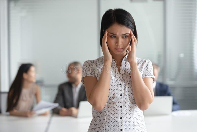 Ο τονισμένος νευρικός ασιατικός υπάλληλος επιχειρησιακών γυναικών αισθάνεται τον πονοκέφαλο στην εργασία στοκ φωτογραφίες με δικαίωμα ελεύθερης χρήσης