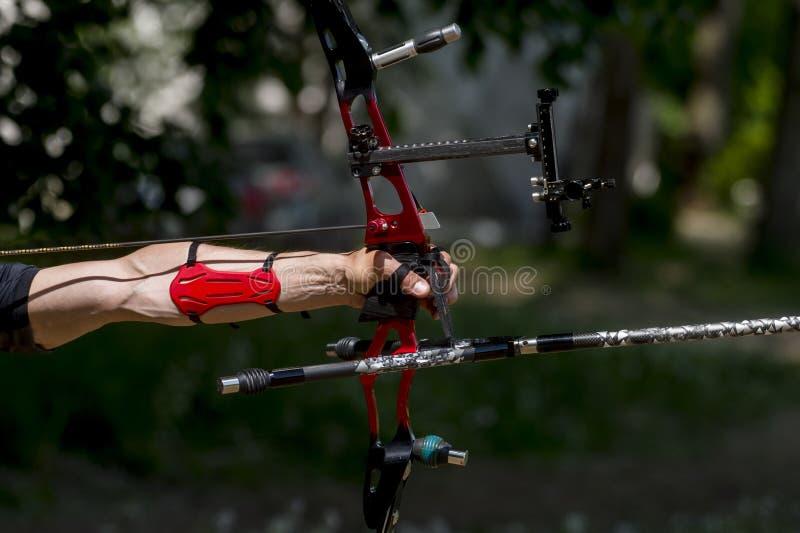 Ο τοξότης τραβά στη σειρά αθλητικών τόξων, που παίρνει το στόχο στο στόχο του στον ανταγωνισμό στοκ εικόνα
