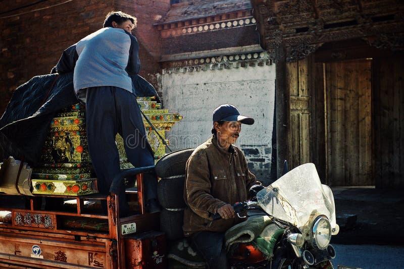ο τοπικός χωρικός δύο μετέφερε τη θιβετιανή βουδιστική λάρνακα σε μια μοτοσικλέτα μπροστά από μια χαρακτηριστική διακοσμημένη πύλ στοκ εικόνα