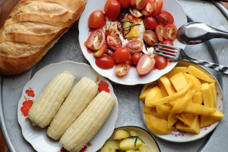 Ο τοπ δίσκος τροφίμων μη κρέατος άποψης, ψωμί, ντομάτα, πατάτα, αυγά, μάγκο, έβρασε το καλαμπόκι στοκ φωτογραφίες