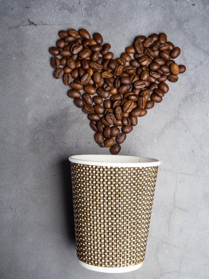 ο τοπ καφές εγγράφου άποψης για να πάει φλυτζάνι και καρδιά έκανε από τα φασόλια καφέ, το διαστημικό, γκρίζο υπόβαθρο αντιγράφων στοκ εικόνες με δικαίωμα ελεύθερης χρήσης