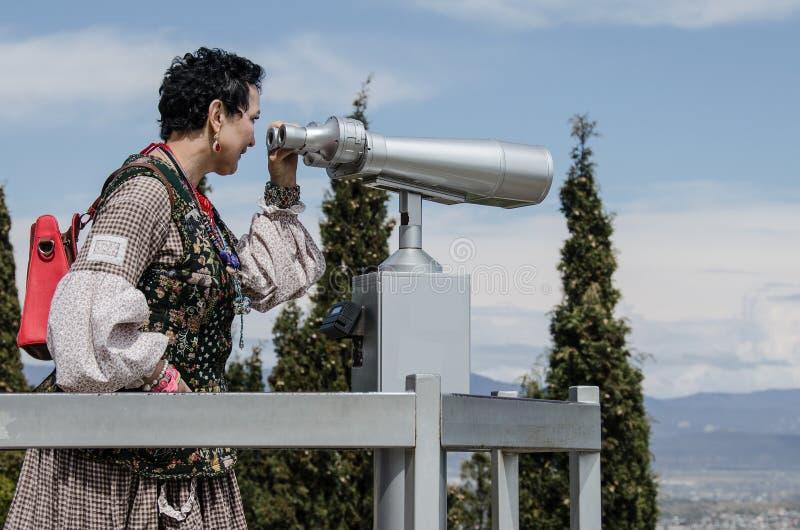 Ο τουρίστας γυναικών εξετάζει τις θέες άνωθεν στοκ εικόνα με δικαίωμα ελεύθερης χρήσης