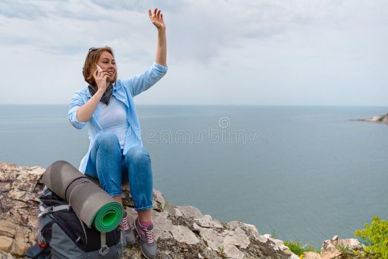 Ο τουρίστας γυναικών σταμάτησε σε μια στάση και αποφάσισε να καλέσει την οικογένειά του στο τηλέφωνο Θάλασσα και ουρανός στο υπόβ στοκ φωτογραφία