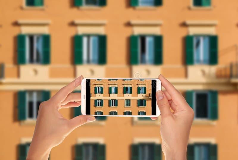Ο τουρίστας κάνει μια φωτογραφία της πρόσοψης ενός πορτοκαλιού ιταλικού κτηρίου στοκ φωτογραφία