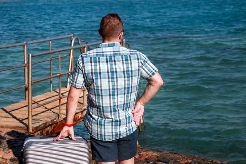 Ο τουρίστας και ο ταξιδιώτης είναι στάση στην παραλία του θερέτρου ξενοδοχείων με την ταξιδεμμένη βαλίτσα, απολαμβάνουν το περιβά στοκ φωτογραφία