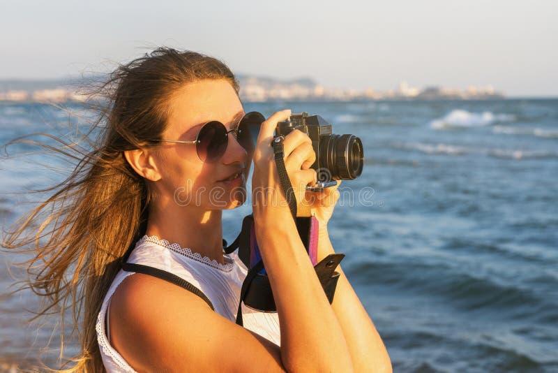 Ο τουρίστας κοριτσιών φωτογραφίζει τις θέες περπατώντας κατά μήκος του περιπάτου κοντά στη θάλασσα στοκ εικόνα