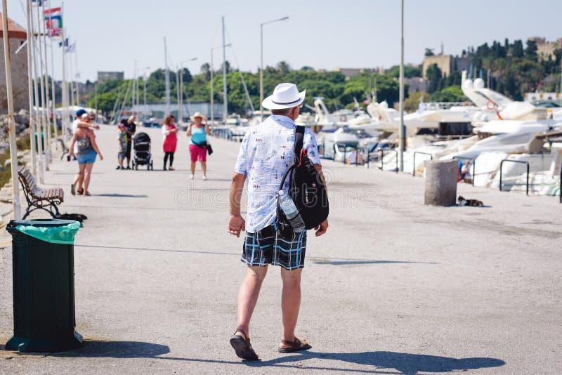 Ο τουρίστας με το σακίδιο στην πλάτη του περπατά κατά μήκος του εν πλω λιμένα περιπάτων της πόλης της Ρόδου Νησί της Ρόδου, Ελλάδ στοκ εικόνα