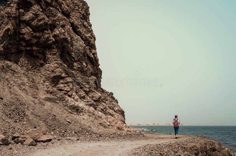 Ο τουρίστας νέων κοριτσιών σε μια κόκκινη ΚΑΠ με ένα σακίδιο πλάτης πηγαίνει κατά μήκος της δύσκολης ακτής της Ερυθράς Θάλασσας σ στοκ εικόνα με δικαίωμα ελεύθερης χρήσης
