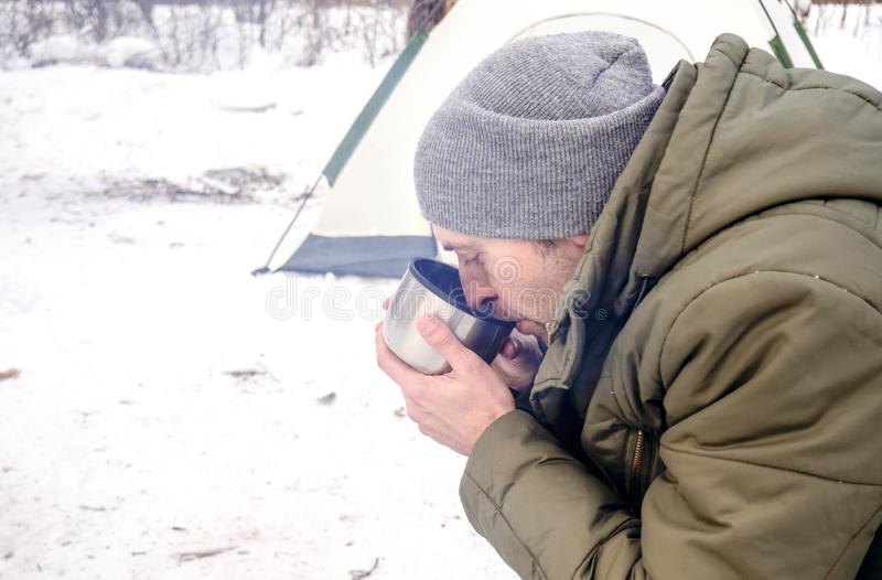Ο τουρίστας πίνει το καυτό τσάι στο χειμερινό δάσος στοκ εικόνα