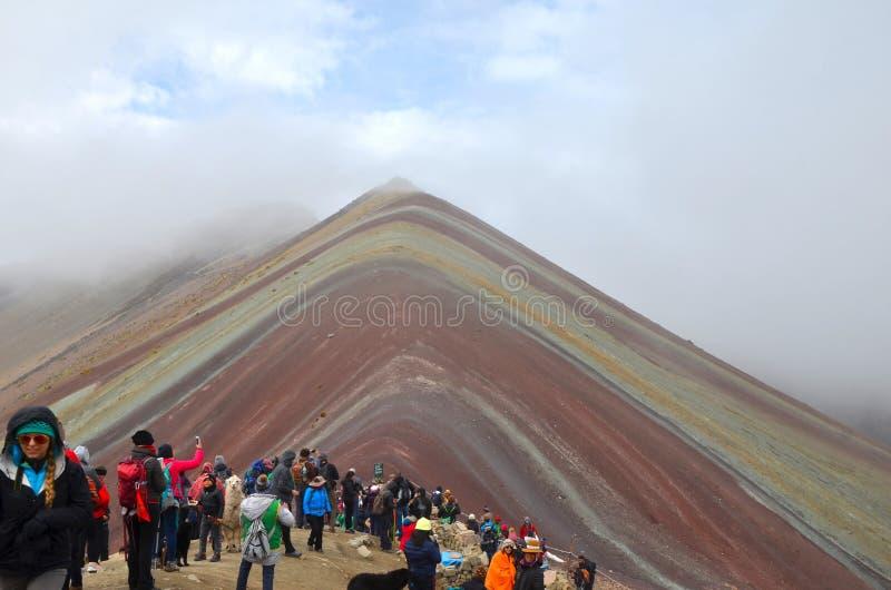 Ο τουρίστας παίρνει μια αναλαμπή του βουνού ουράνιων τόξων Vinicunca στο Περού μέσω των σύννεφων στοκ εικόνες
