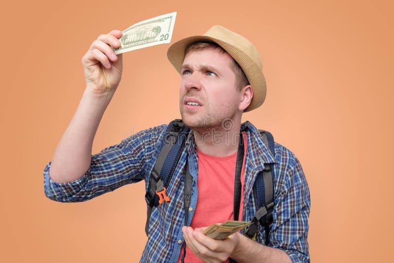 Ο τουρίστας στο καπέλο κρατά το τραπεζογραμμάτιο δολαρίων ελέγχοντας το στοκ εικόνες