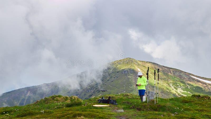 Ο τουρίστας τύπων προωθεί quadrocopter στα βουνά στοκ εικόνες
