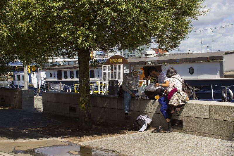 Ο τουρίστας χαλαρώνει και διάβασε σε έναν τοίχο στην ακτή του σύγχρονου Μπέλφαστ εκτός από την ολλανδική φορτηγίδα MV Confiance στοκ εικόνες με δικαίωμα ελεύθερης χρήσης
