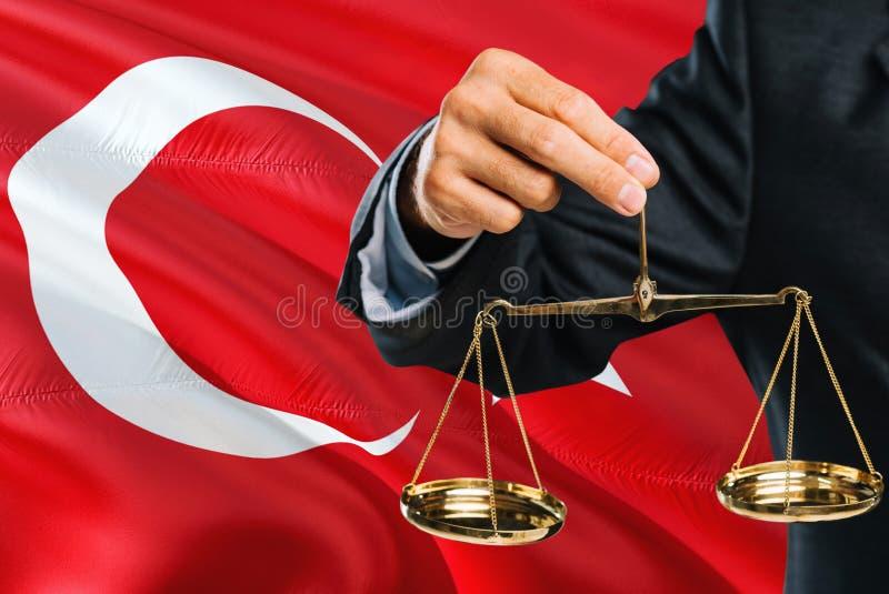 Ο τουρκικός δικαστής κρατά τις χρυσές κλίμακες της δικαιοσύνης με το κυματίζοντας υπόβαθρο σημαιών της Τουρκίας Θέμα ισότητας και στοκ φωτογραφία