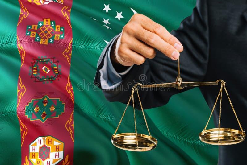 Ο τουρκμενικός δικαστής κρατά τις χρυσές κλίμακες της δικαιοσύνης με το κυματίζοντας υπόβαθρο σημαιών του Τουρκμενιστάν Θέμα ισότ στοκ φωτογραφία με δικαίωμα ελεύθερης χρήσης