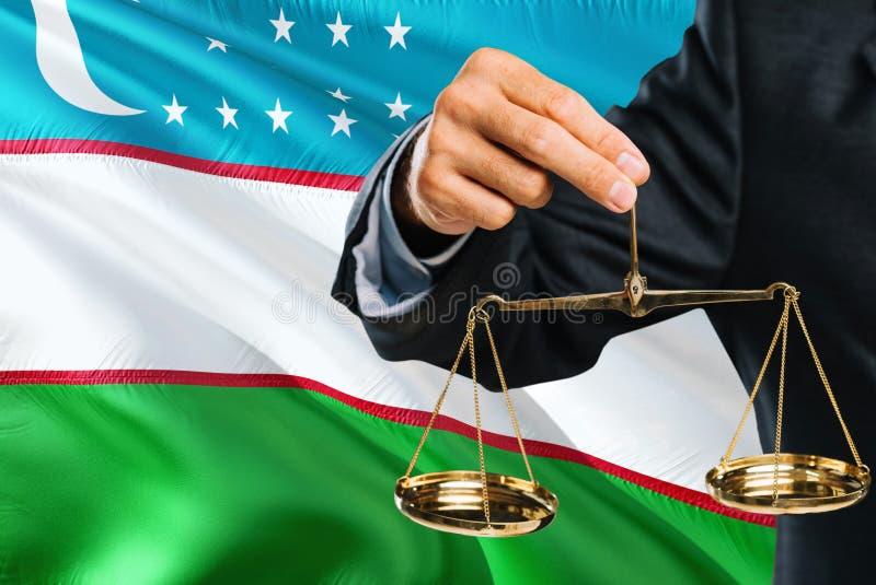 Ο του Ουζμπεκιστάν δικαστής κρατά τις χρυσές κλίμακες της δικαιοσύνης με το κυματίζοντας υπόβαθρο σημαιών του Ουζμπεκιστάν Θέμα ι στοκ εικόνες με δικαίωμα ελεύθερης χρήσης