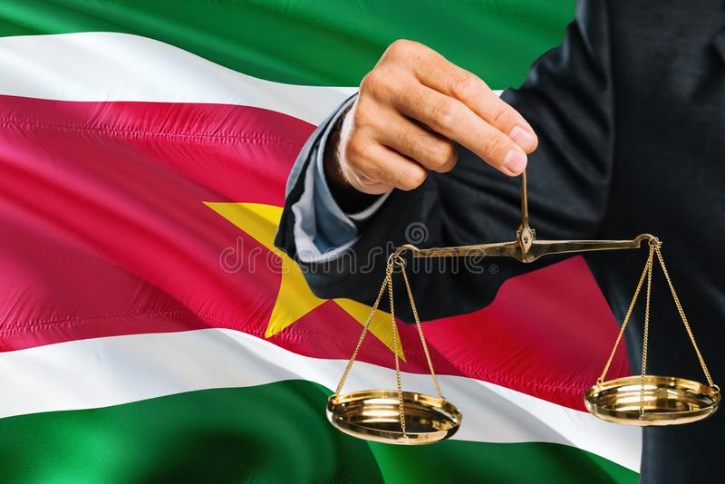 Ο του Σουρινάμ δικαστής κρατά τις χρυσές κλίμακες της δικαιοσύνης με το Σουρινάμ κυματίζοντας το υπόβαθρο σημαιών Θέμα ισότητας κ στοκ φωτογραφία