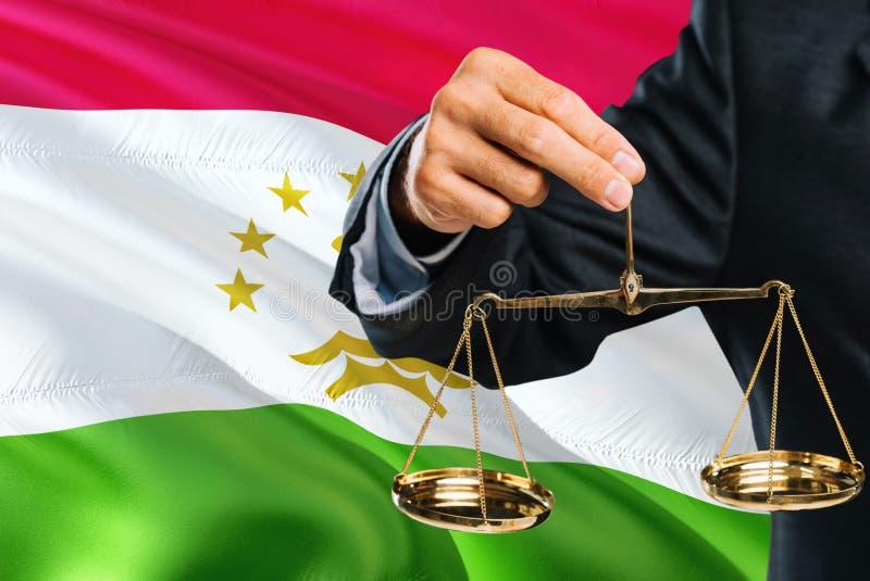 Ο του Τατζικιστάν δικαστής κρατά τις χρυσές κλίμακες της δικαιοσύνης με το κυματίζοντας υπόβαθρο σημαιών του Τατζικιστάν Θέμα ισό στοκ φωτογραφία με δικαίωμα ελεύθερης χρήσης