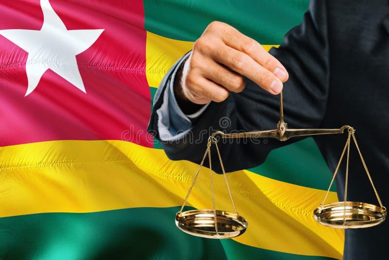 Ο του Τόγκο δικαστής κρατά τις χρυσές κλίμακες της δικαιοσύνης με το κυματίζοντας υπόβαθρο σημαιών του Τόγκο Θέμα ισότητας και νο στοκ εικόνες με δικαίωμα ελεύθερης χρήσης