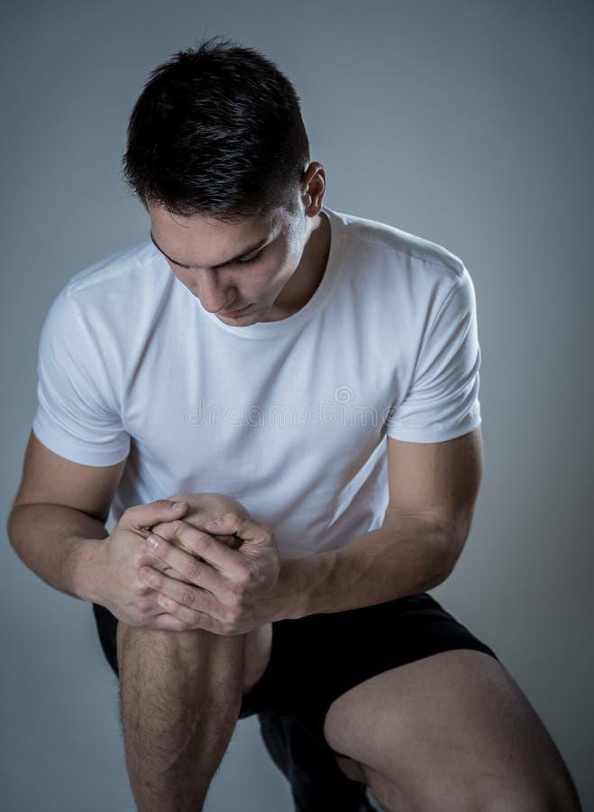 Ο το αθλητής τραυμάτισε κατά άσκηση ή την τρέξιμο κρατώντας το γόνατό του στον πόνο στοκ φωτογραφία με δικαίωμα ελεύθερης χρήσης