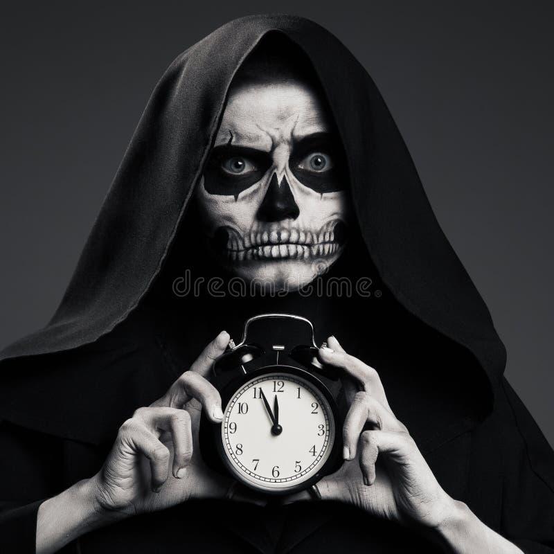 Ο τρομακτικός θάνατος κρατά ένα ρολόι στο χέρι του στοκ φωτογραφία με δικαίωμα ελεύθερης χρήσης
